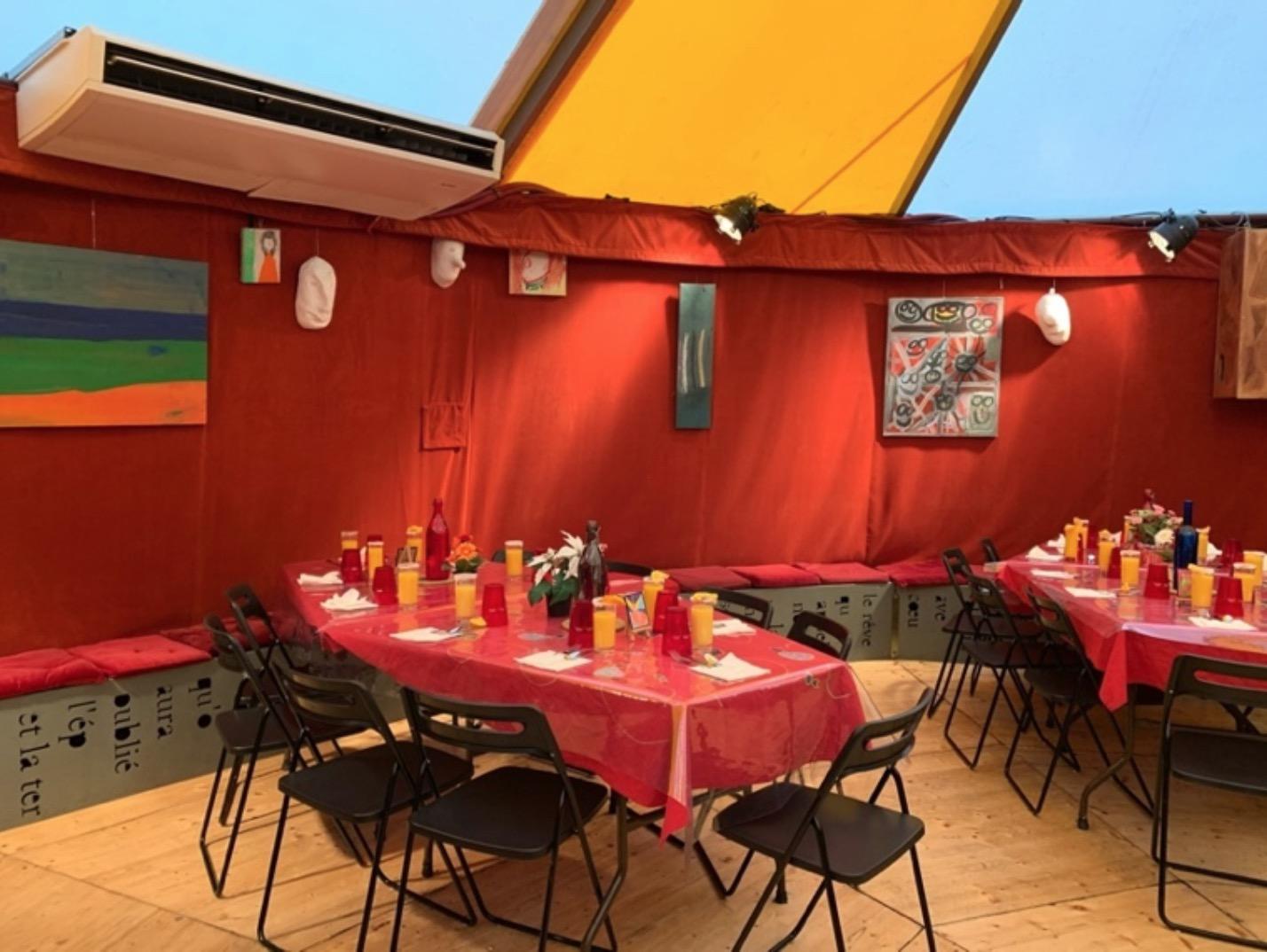 Sous le petit chapiteau, les tables sont mises au cordeau. Les murs sont décorés d'œuvres réalisées dans les ateliers.